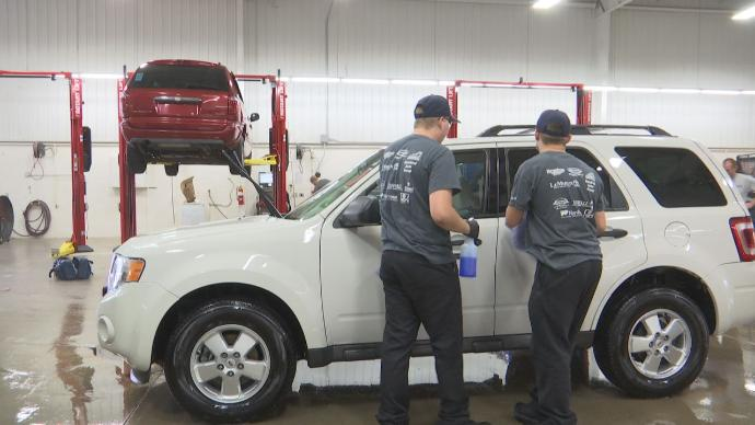 image of students working on car